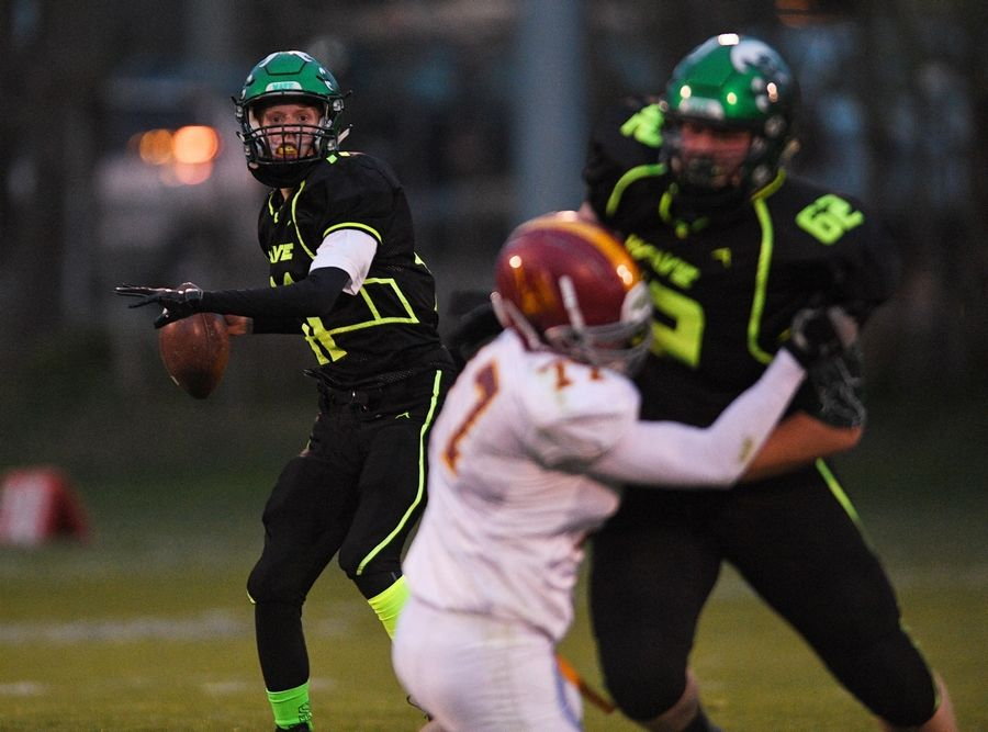 St. Edward quarterback Zeke Rolando looks downfield as lineman Tristan Merlin blocks Westmont's Logan Hicks in a Monday night football game in Elgin on Monday.