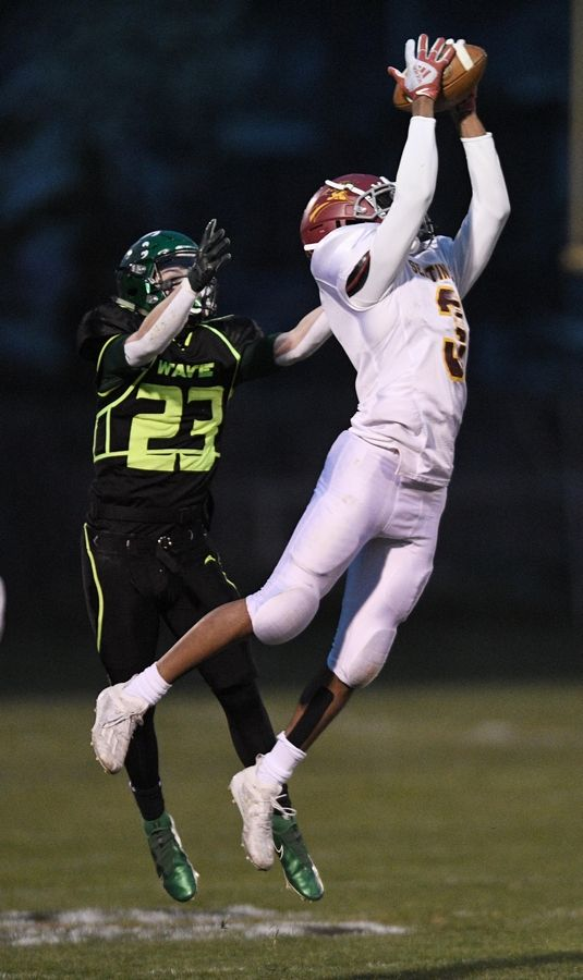 Westmont's Braelen Jones catches a pass as St. Edward's Joseph Sacco defends in a Monday night football game in Elgin on Monday, April 19, 2021.