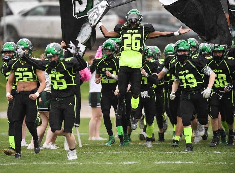 St. Edward Green Wave burst through the team banner to start a Monday night football game against Westmont in Elgin on Monday, April 19, 2021.