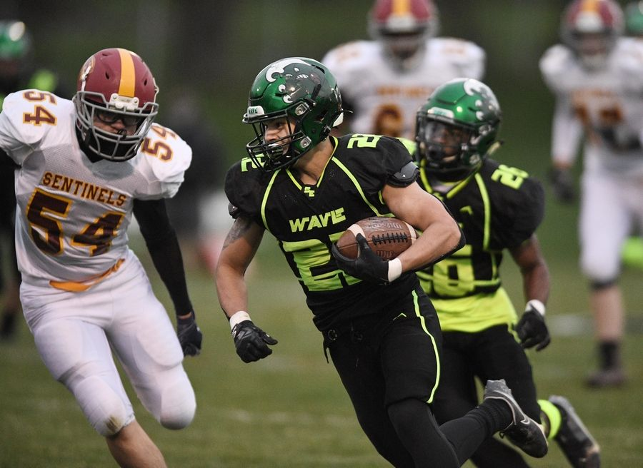 St. Edward's Anthony Kirkwood runs as Westmont's James Mendoza chases him in a Monday night football game in Elgin on Monday, April 19, 2021.