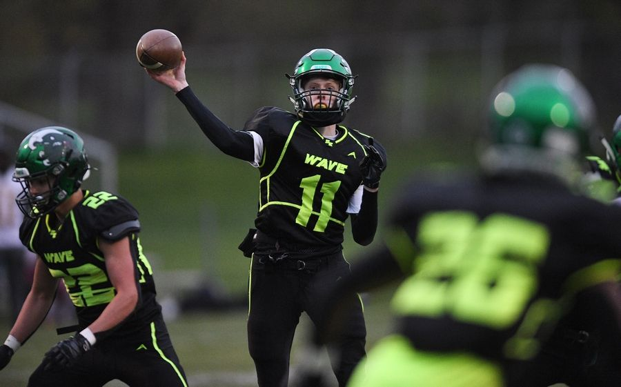 St. Edward quarterback Zeke Rolando throws a pass to Clemon McCullough II in a Monday night football game against Westmont in Elgin on Monday, April 19, 2021.