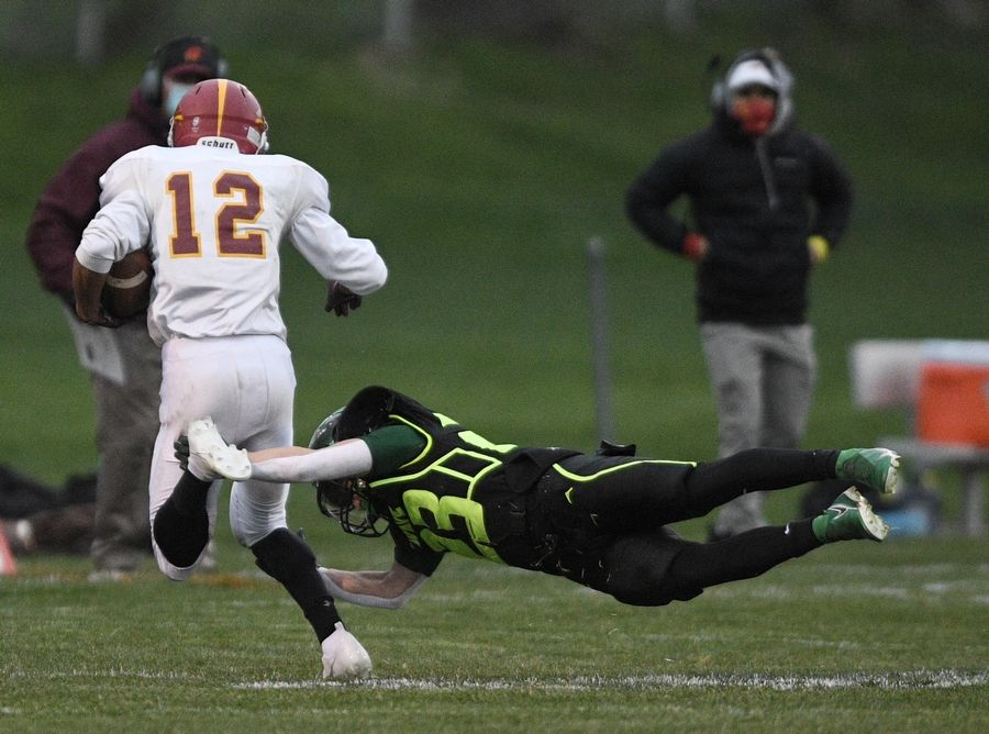 St. Edward's Joseph Sacco dives for the legs of Westmont's Jacob LoCoco in a Monday night football game in Elgin on Monday, April 19, 2021.