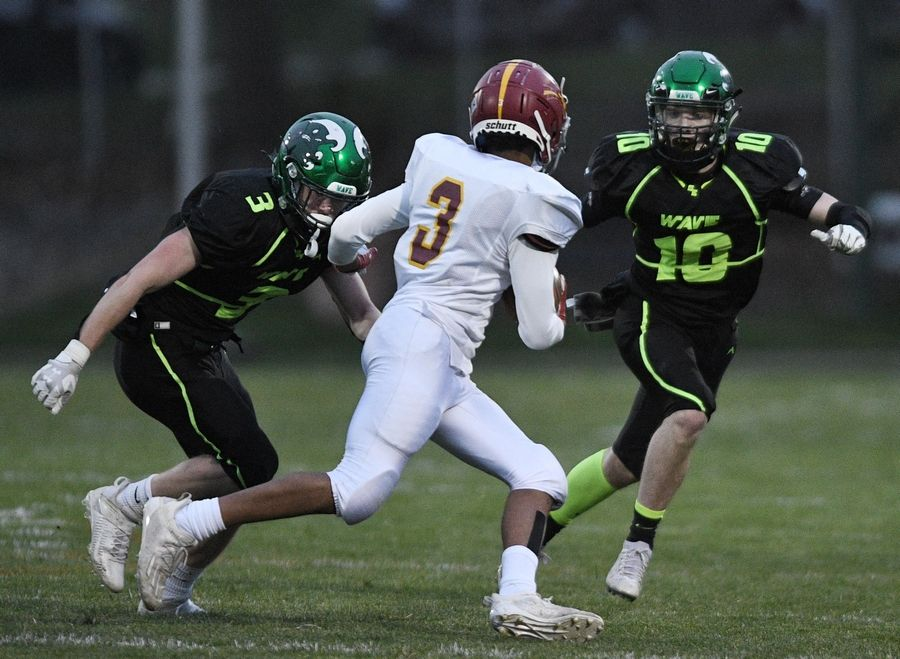 St. Edward's Erik Hill and Liam Pomeroy, right, corral Westmont's Braelen Jones in a Monday night football game in Elgin on Monday, April 19, 2021.
