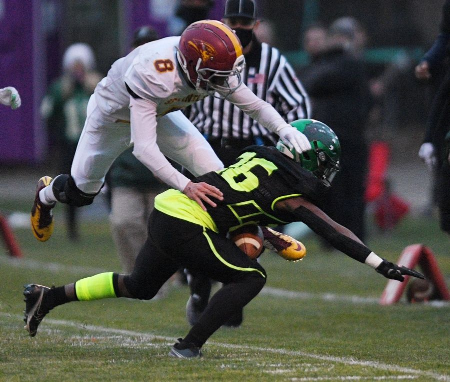 St. Edward's Clemon Mccullough II is forced out of bounds by Westmont's Ryan Domin in a Monday night football game in Elgin on Monday, April 19, 2021.