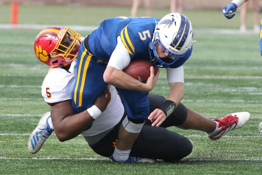 Batavia defensive lineman Fikayo Afolarin tackles Wheaton North quarterback Mark Forcucci Saturday afternoon at Huskie Stadium in DeKalb.