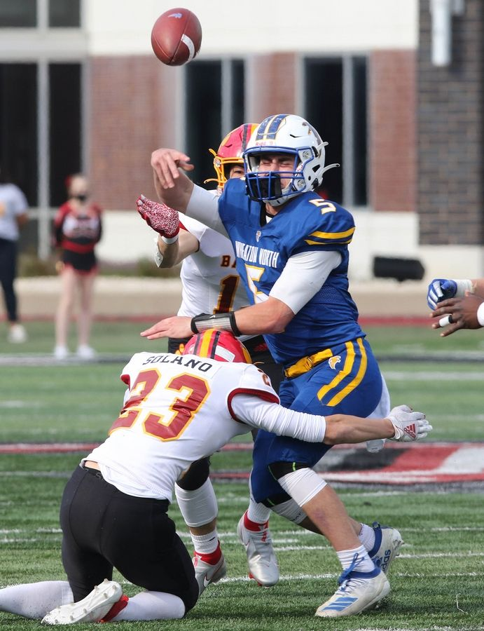 Wheaton North quarterback Mark Forcucci is hit as he throws by Batavia defensive back Vincie Solano during their game Saturday afternoon in Huskie Stadium at Northern Illinois University.