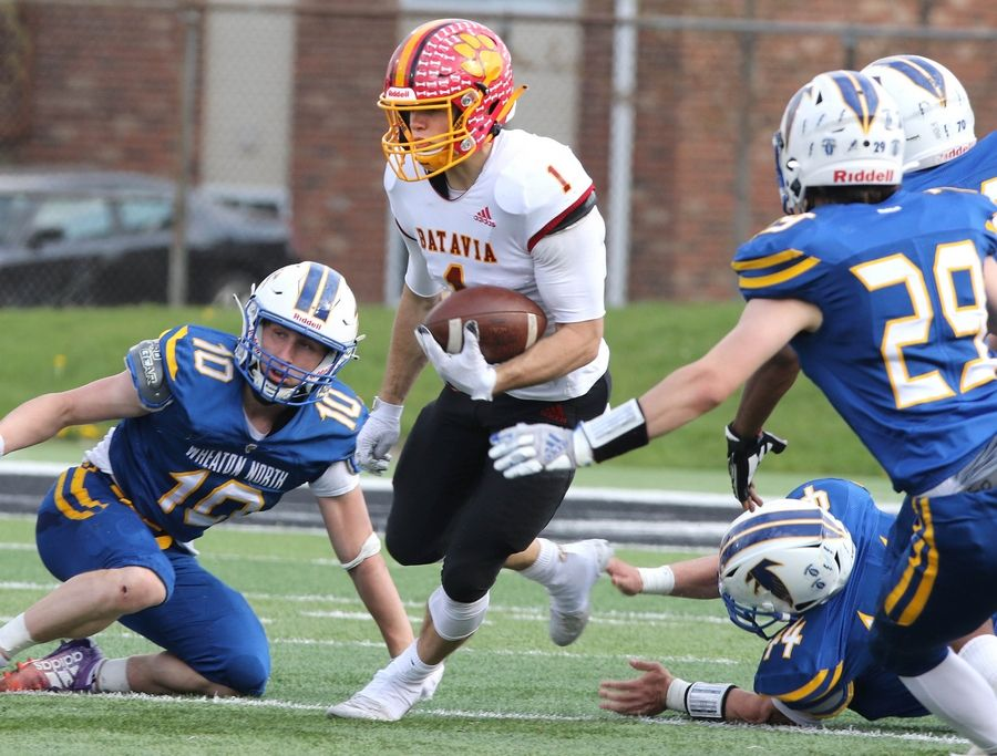 Batavia quarterback Trey Urwiler scrambles for yardage as he is pressured by the Wheaton North defense during their game Saturday afternoon in Huskie Stadium at Northern Illinois University.
