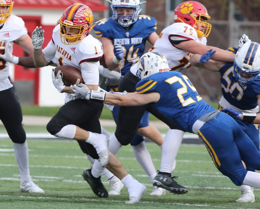 Batavia quarterback Trey Urwiler escapes the tackle of Wheaton North safety Jackson Moore during their game Saturday afternoon in Huskie Stadium at Northern Illinois University.