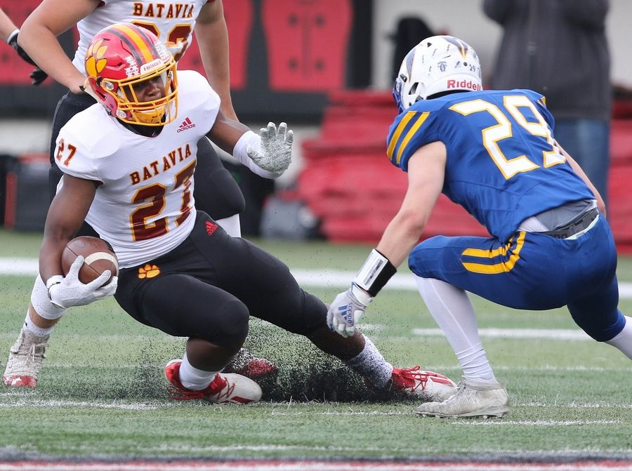 Batavia running back Jalen Buckley slips down trying to put a move on Wheaton North safety Jackson Moore during their game Saturday afternoon in Huskie Stadium at Northern Illinois University.