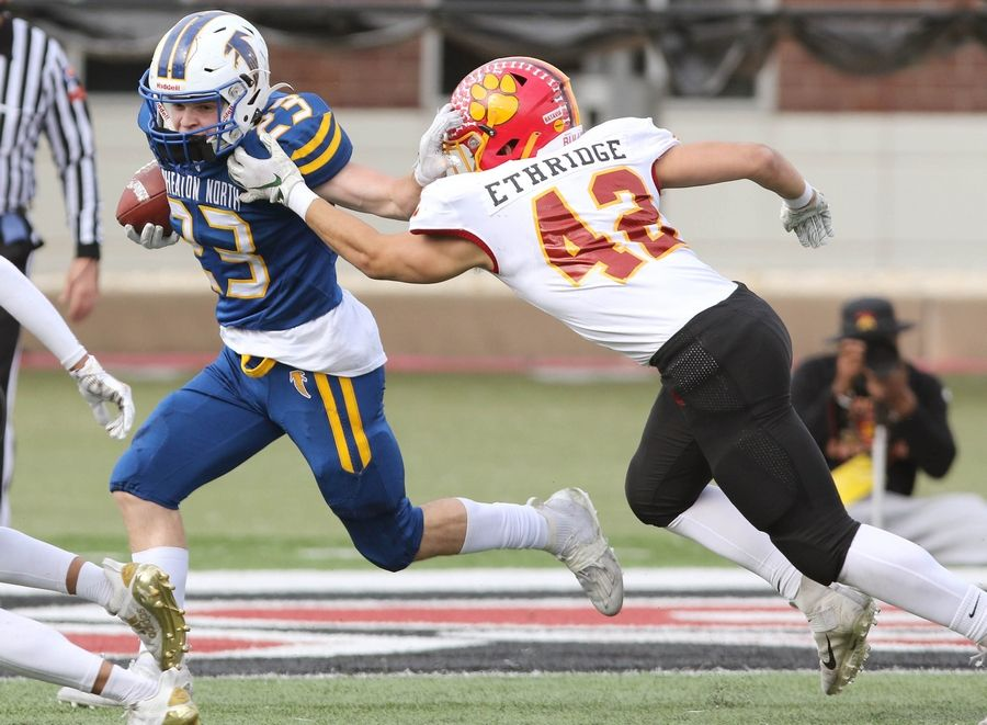 Wheaton North running back Brayton Maske fends off the tackle of Batavia linebacker Ethan Ethridge during their game Saturday afternoon in Huskie Stadium at Northern Illinois University.