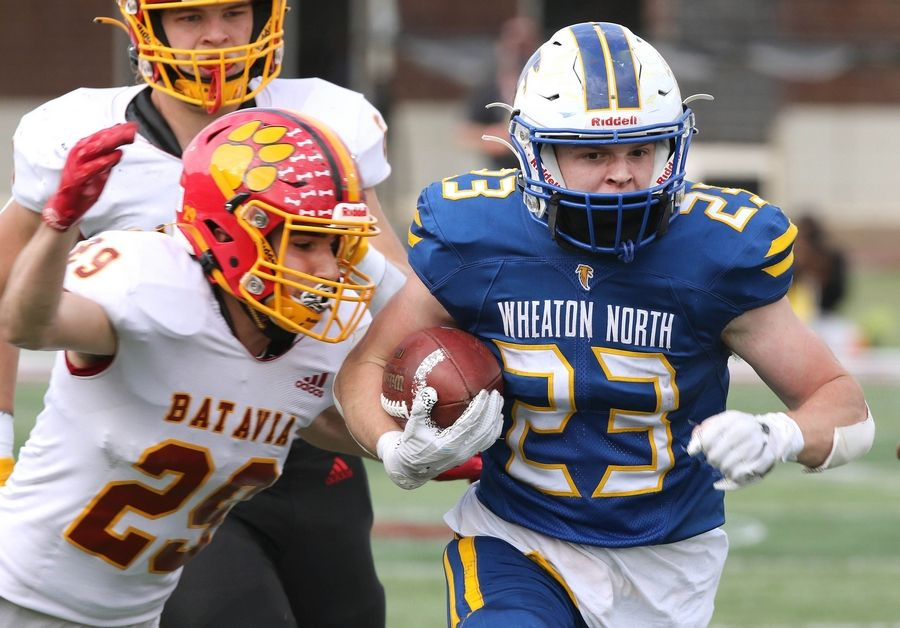 Wheaton North running back Brayton Maske picks up big yards as Batavia defensive back Anthony Bradley tries to strip the ball from behind during their game Saturday afternoon in Huskie Stadium at Northern Illinois University.