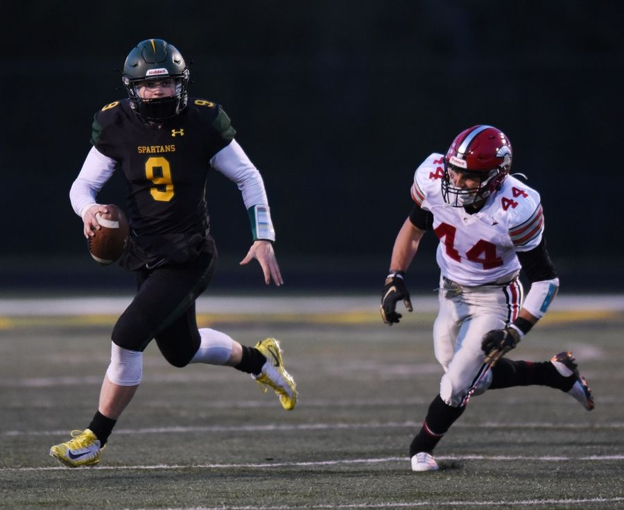 Glenbrook North quarterback Avery Burow looks downfield with Deerfield's Vincent Sciarrone following in pursuit during Friday's game in Northbrook.
