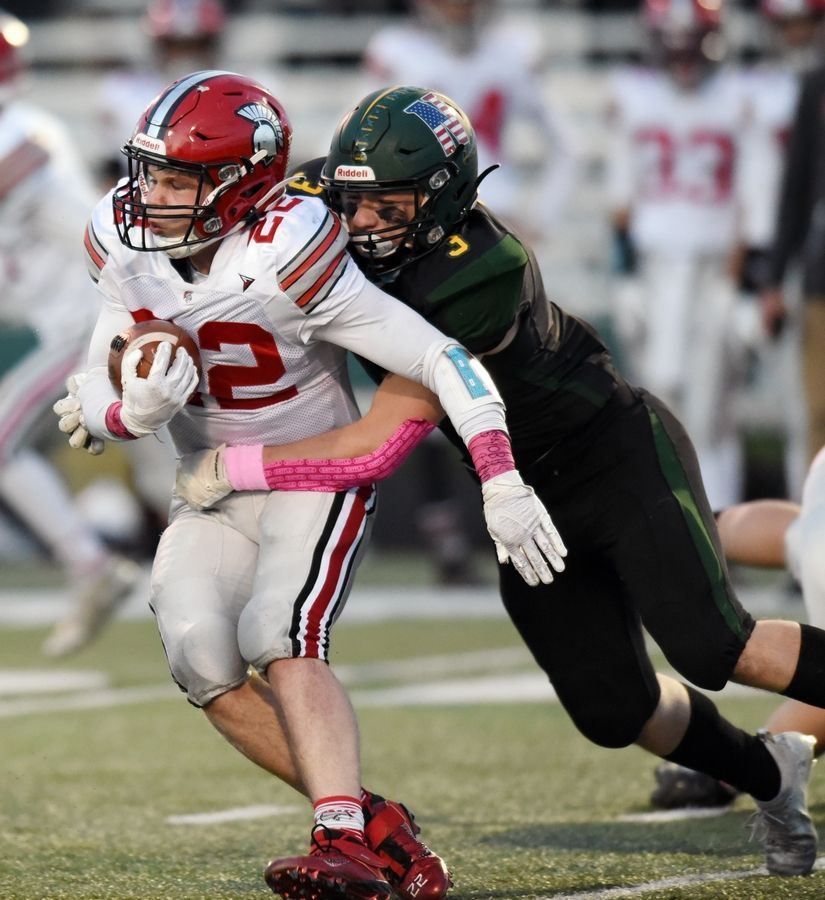 Deerfield's Luke Woodson gets tackled by Glenbrook North's JR Flood during Friday's game in Northbrook.