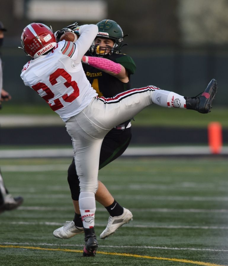 Deerfield's Zachary Pomerantz (23) gets hit by Glenbrook North's Ryan Henschel on a pass completion during Friday's game in Northbrook.