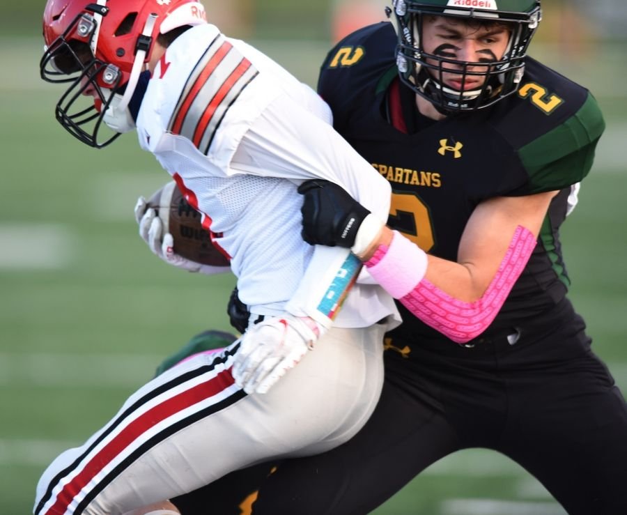 Glenbrook North's Luke Henry, right, tackles Deerfield's Luke Jones on the kickoff return of Friday's game in Northbrook.