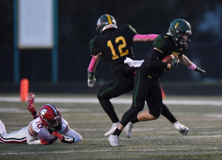 Glenbrook North's Zach Mendo, right, takes the ball from Murphy Mulvihill on a reverse as Deerfield's Jonathan Ybarra misses a tackle during Friday's game in Northbrook.