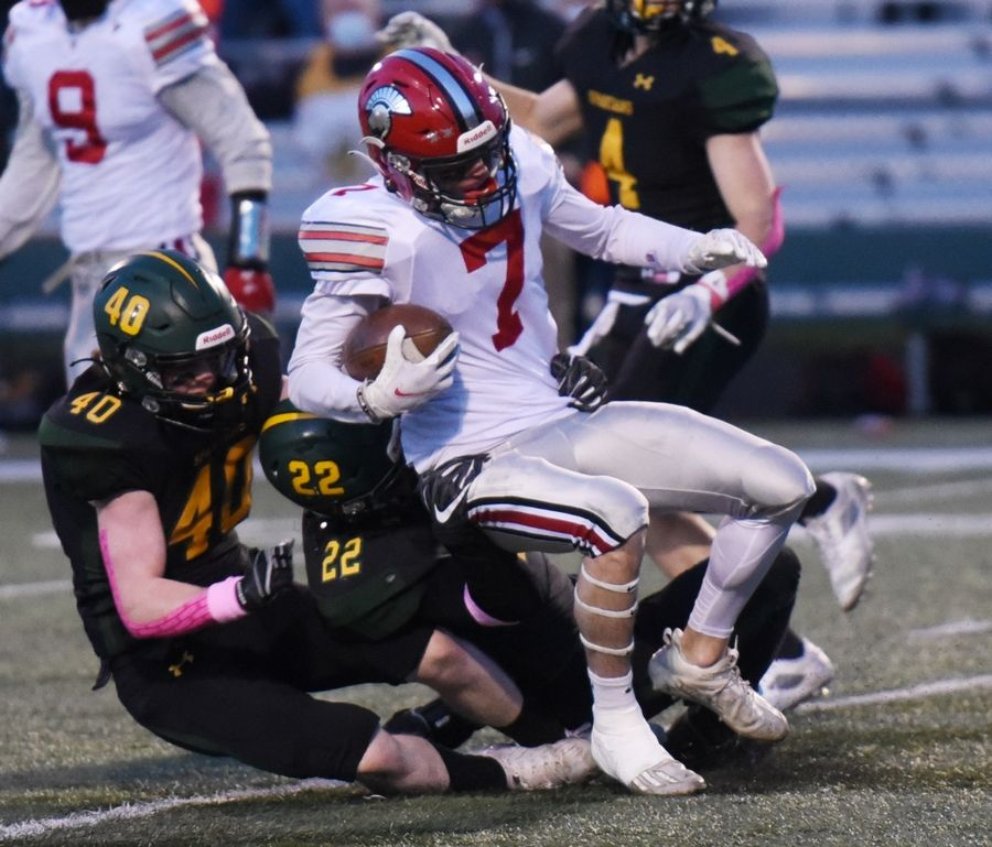 Deerfield's Luke Jones is tackled by Glenbrook North's Drake Marquez (22) and Quinn Clarke during Friday's game in Northbrook.