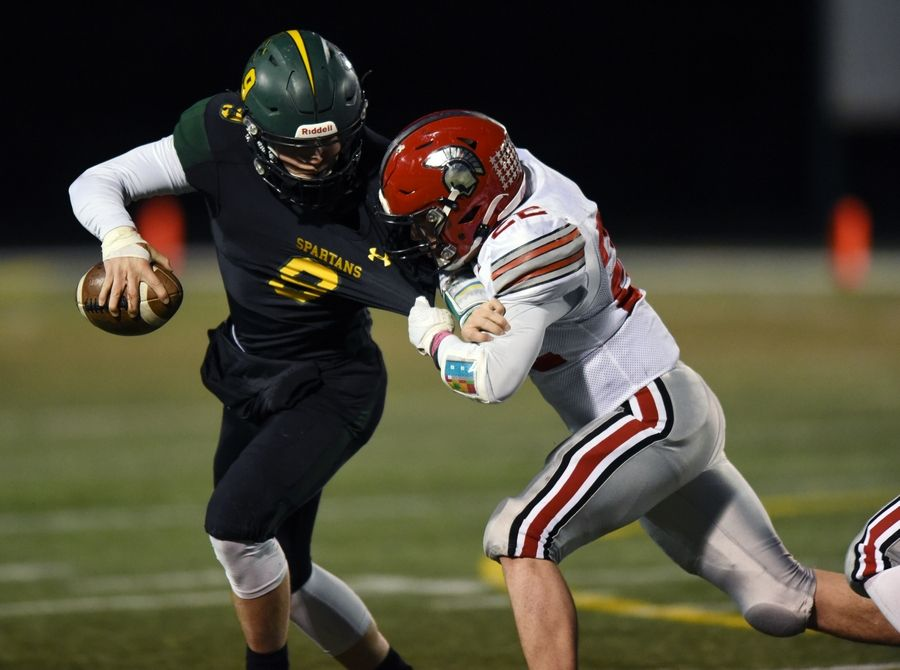 Glenbrook North quarterback Avery Burow tries to fend off Deerfield's Luke Woodson during Friday's game in Northbrook. The Spartans fell to the Warriors 18-3 to end the pandemic-delayed and shortened season. Burow exited the game in an ambulance following a hard hit in the third quarter.Story and photos on Page 20