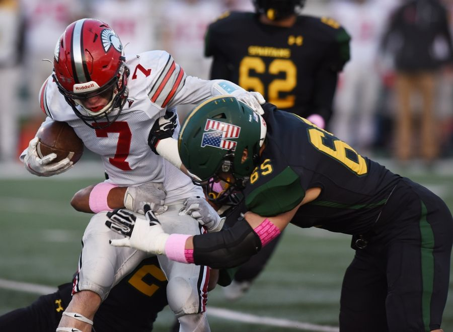 Glenbrook North's Matt Karis, right, and Juan Saenz, rear, tackle Deerfield's Luke Jones during Friday's game in Northbrook.
